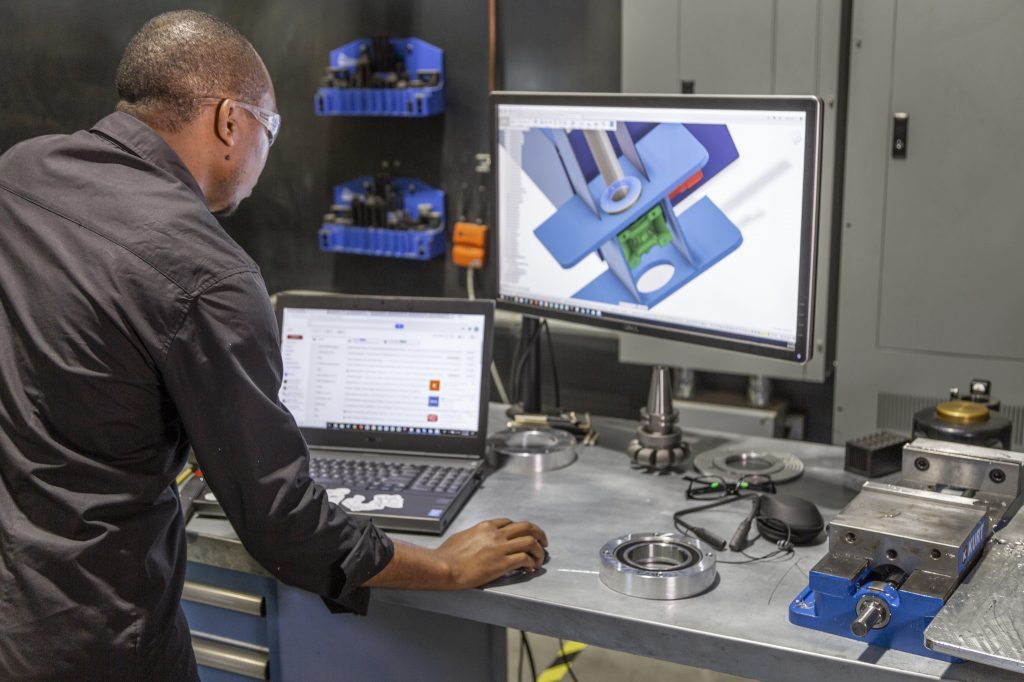 An engineer using Autodesk's Fusion 360 software.