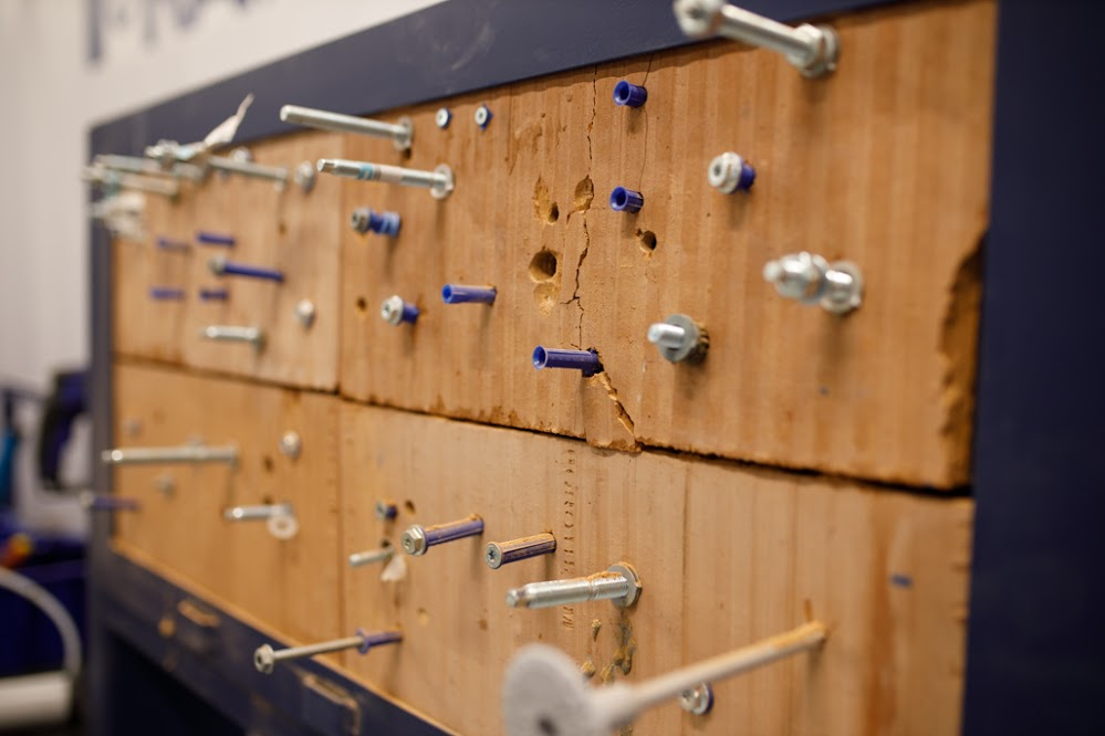 A cork board with several different mountings and fixtures attached.