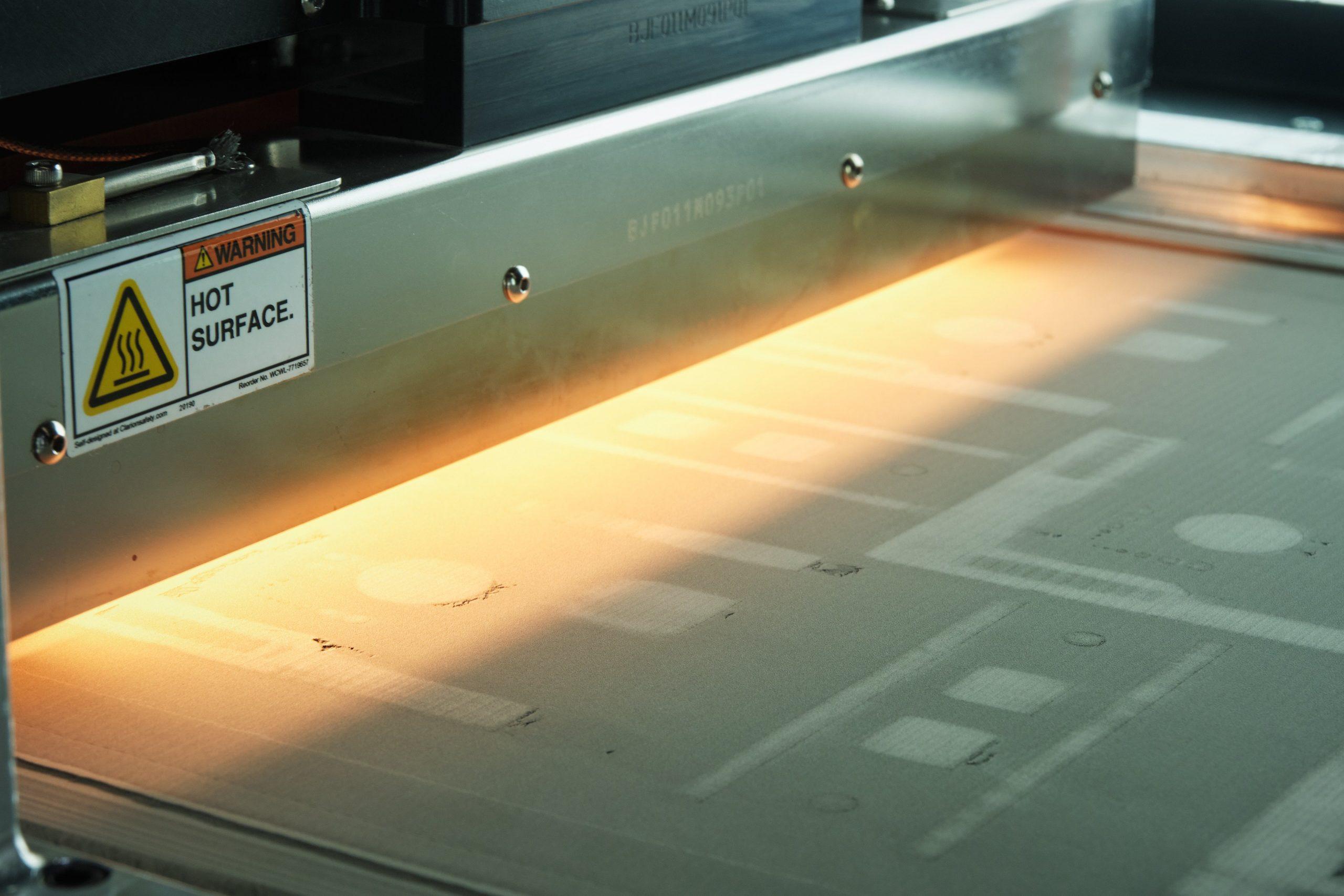 The binder jet 3D printing process on GE Additive's H2 machine. Photo via Cummins Inc.