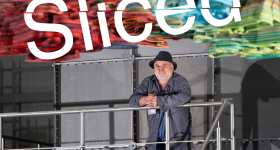 The Sliced logo on top of an image of Peter Lang and his 3D printed acoustic artwork.