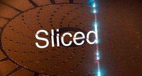 Sliced logo on an image of the Calibur3's powder bed. Photo via Wayland Additive.
