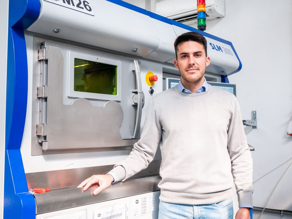 BEAMIT's Alessandro Rizzi alongside an SLM 3D printer.