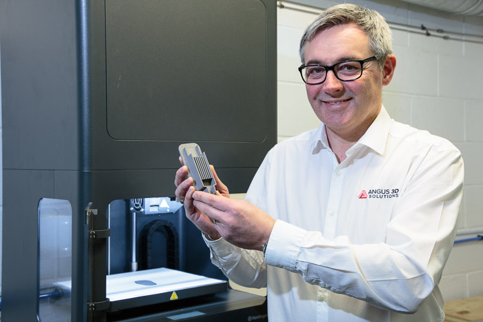 Andy Simpson, Managing Director at Angus 3D Solutions, with a Metal X 3D printed part. Photo via Markforged.