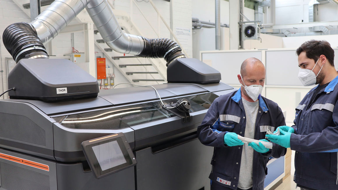 Two Volkswagen employees check the quality of structural parts produced using the binder jetting process for car production in front of the prototype of the binder printer at the high-tech 3D printing center in Wolfsburg. Photo via Volkswagen.