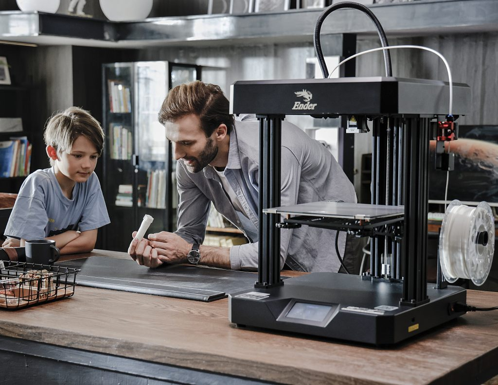 A father and son using an Ender7 3D printer.