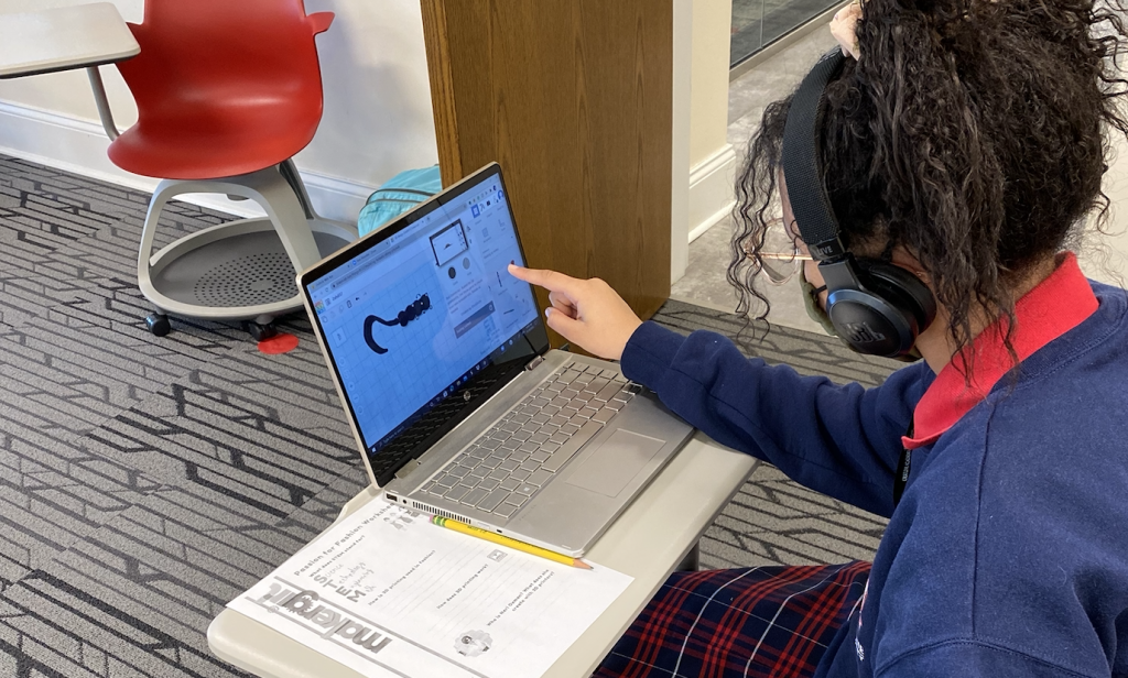 A student designing a 3D printed part on a laptop.