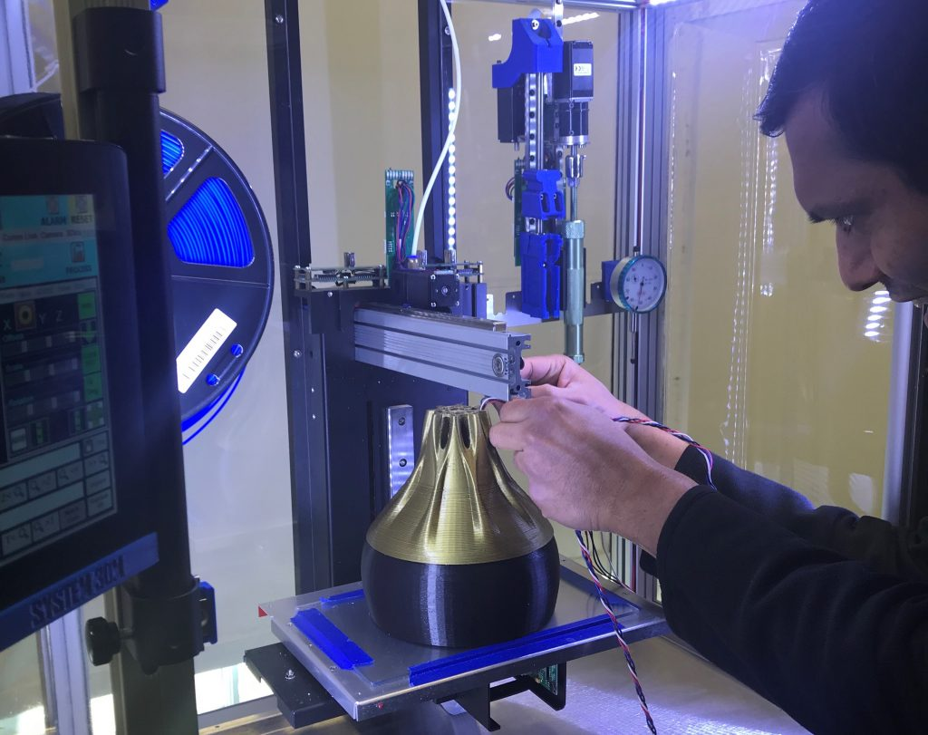 An engineer 3D printing a lighting component.