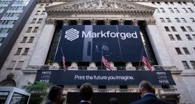 Traders looking up at a Markforged sign outside the NYSE.