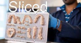 The Sliced logo on top of a tray of Nexa3D dental 3D printed prosthetics.