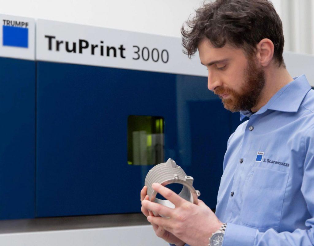 An engineer holding a 3D printer part alongside TRUMPF's TruPrint 3000.