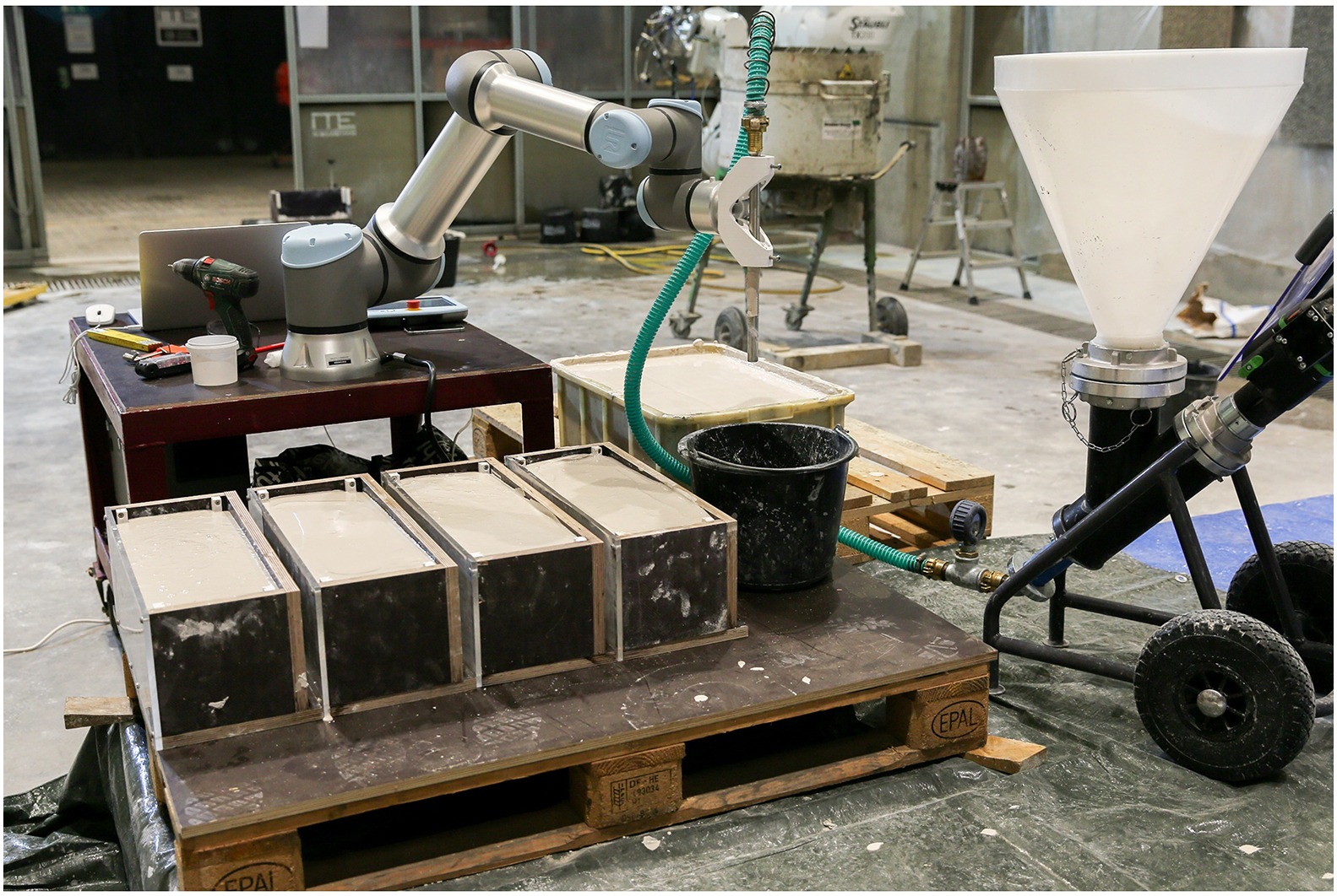 Injection 3D Concrete Printing setup: mixer, pump, robot, and formwork filled with ground limestone suspension. Photo via TU Braunschweig.