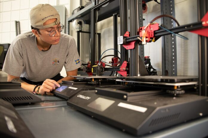 Bioengineering student Jack Roeder uses 3D printing equipment at University of Louisville's Additive Manufacturing Institute of Science and Technology. Photo via UofL.