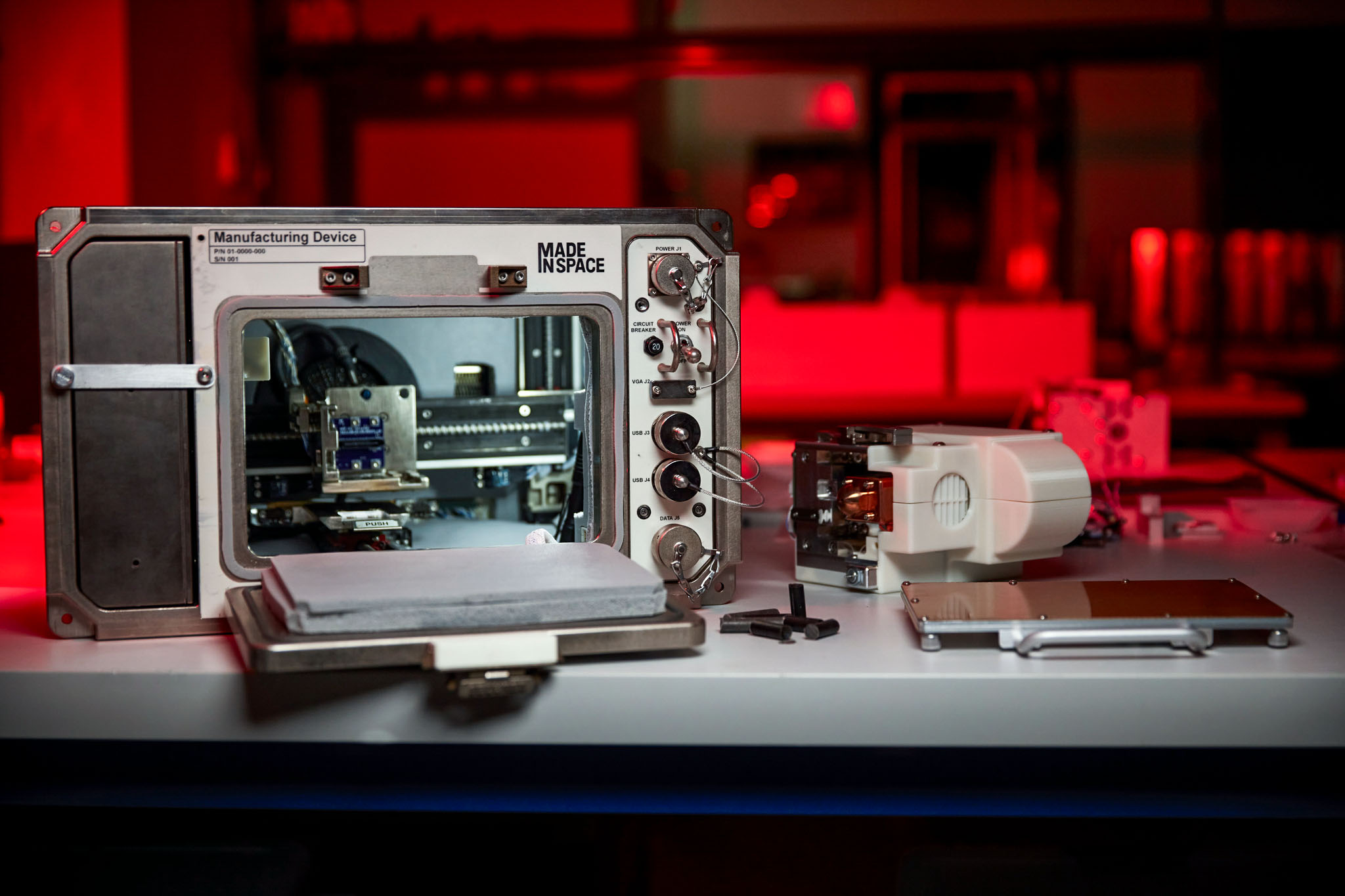 The Redwire Regolith Print facility suite, consisting of Redwire's Additive Manufacturing Facility, and the print heads, plates and lunar regolith simulant feedstock that will be launching to the International Space Station. Photo via Redwire.