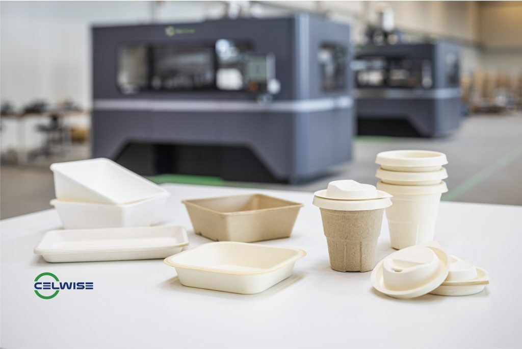 Celwise's sustainable molded fiber products, which replace single-use plastics, in front of the X1 160Pro production metal 3D printer. Photo via ExOne.